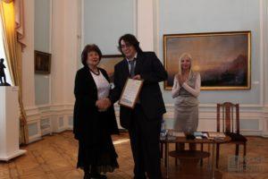 Директор музея Наталья Вавилова вручает благодарственное письмо программисту из группы разработчиков Максиму Щербанничу